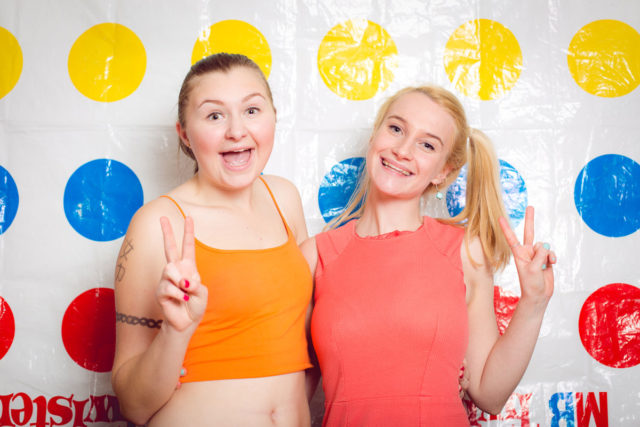 Two girls posing with a peace sign in front of a twister backdrop