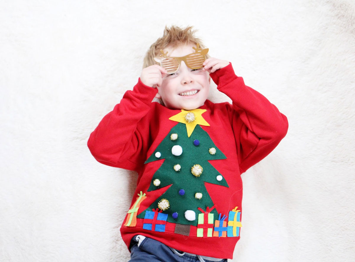 blonde boy wearing ugly xmas sweater and yellow kanye west glasses