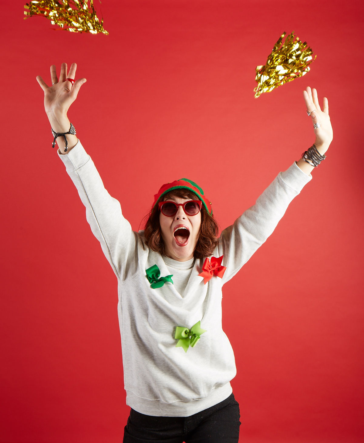 Woman with hands in the air and mouth open with shiny gold paper floating down