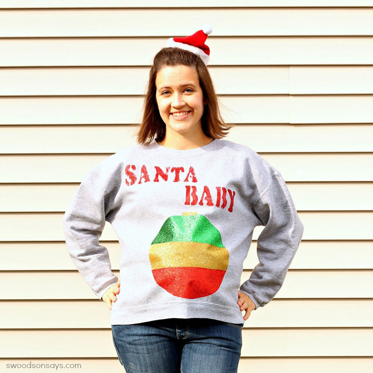 pregnant woman wearing an xmas sweater with santa baby writing