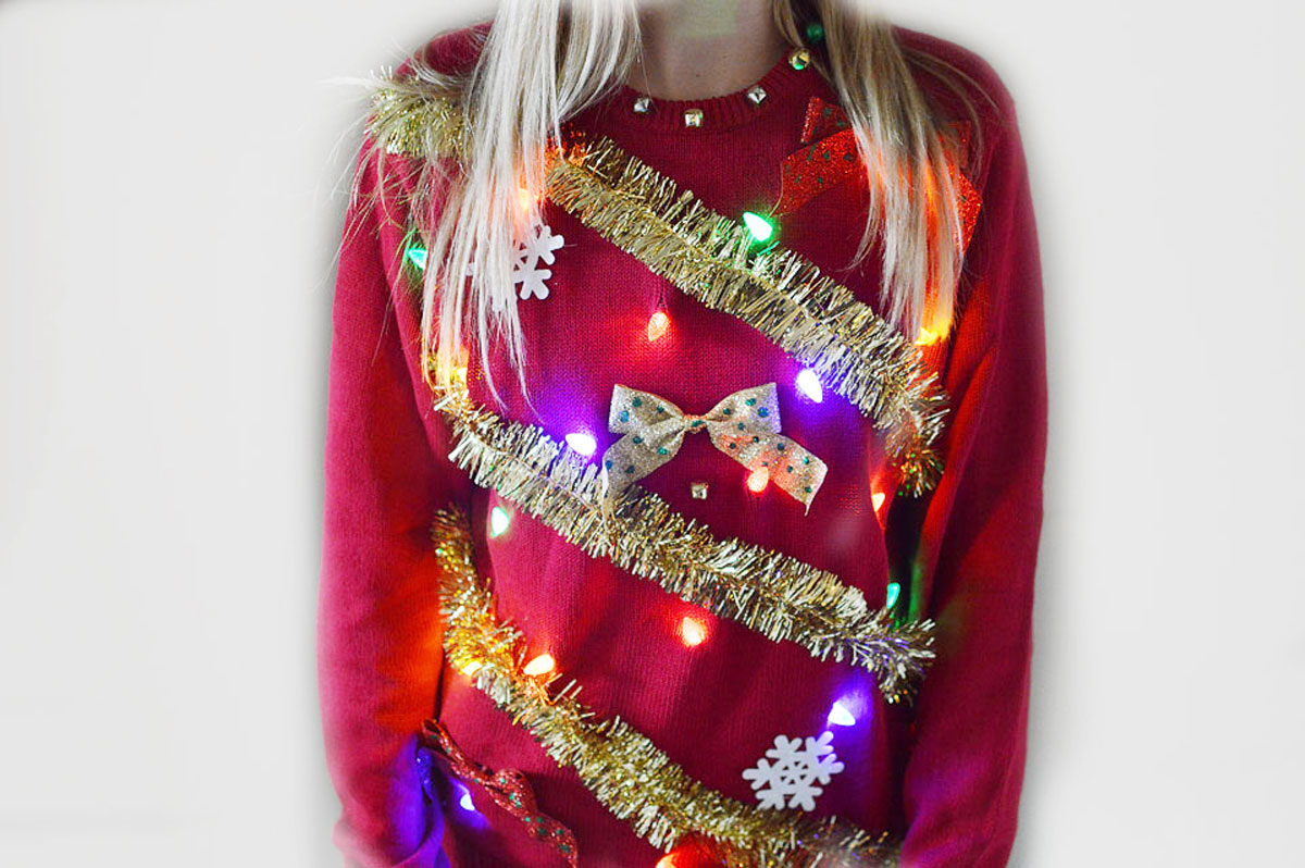 woman wearing a sweater tinsel with lights sweater