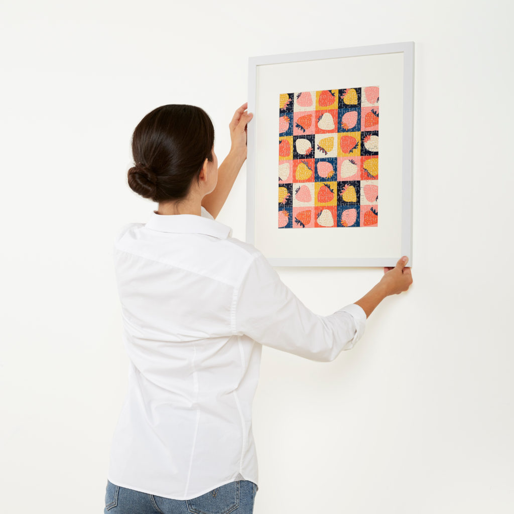 lady hanging a framed puzzle