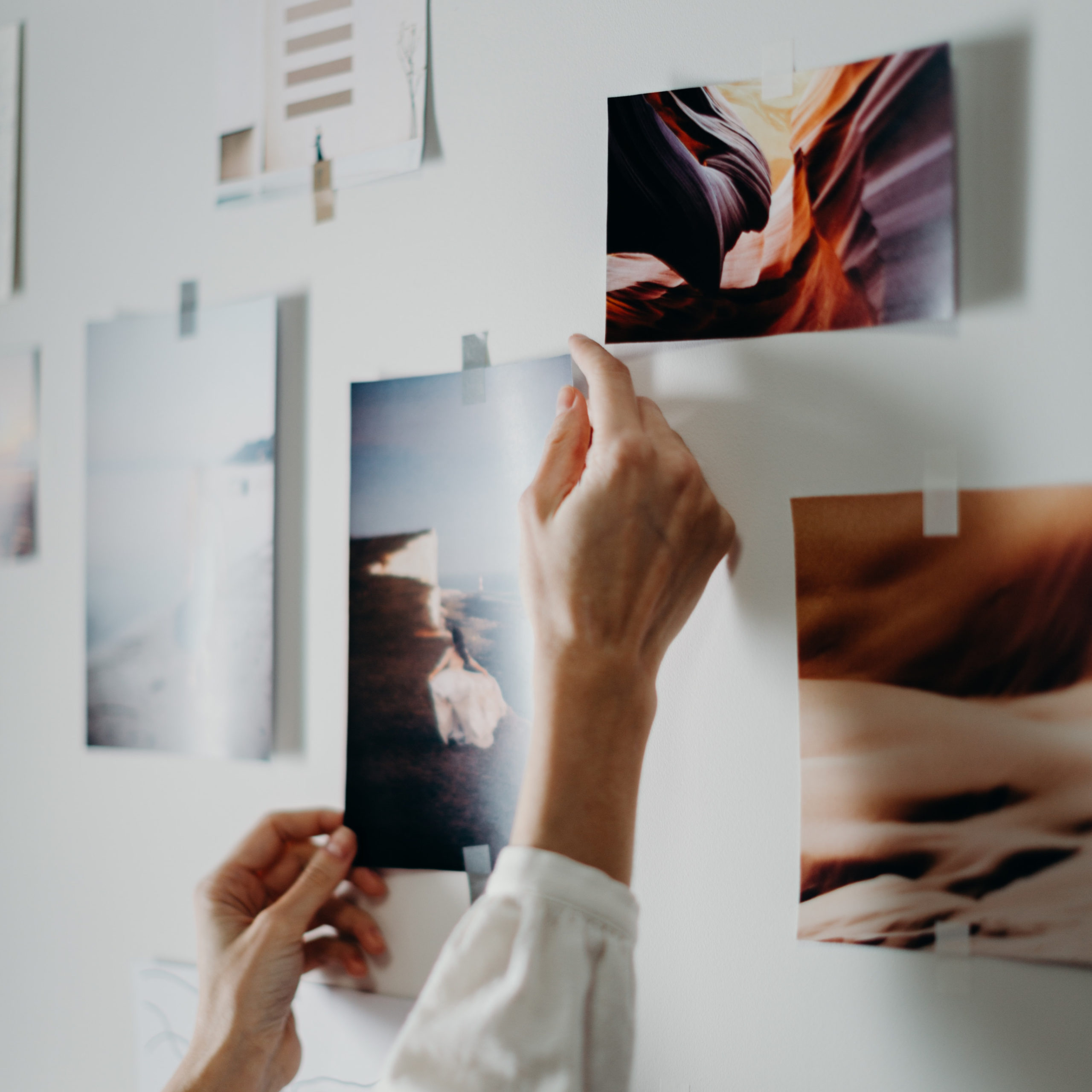 photo of person putting photos on a wall with washi tape