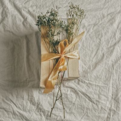 Photo of a Gift wrapped with dried flowers and a satin bow