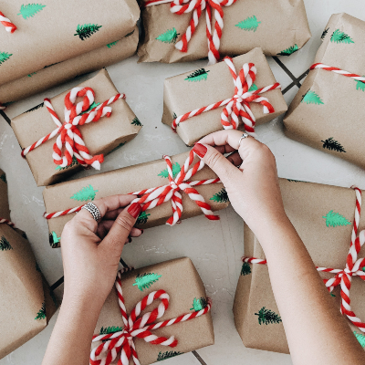 photo of Gifts in brown wrapping paper with foil fir trees and a candy-striped yarn