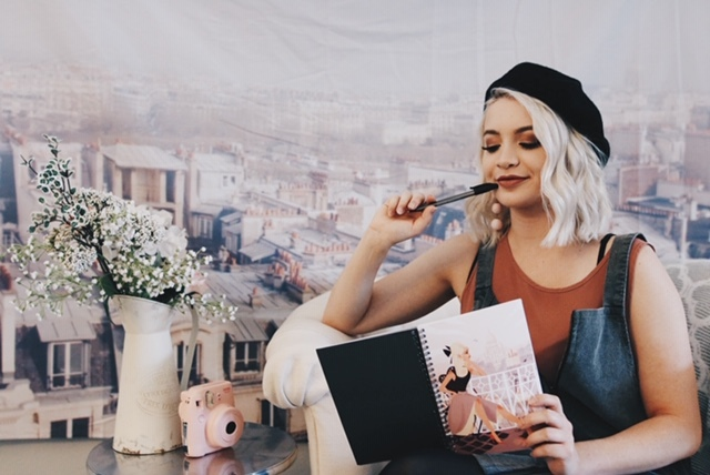 a picture with a woman holding a notebook and a pen