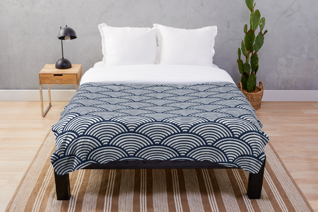 photo of a bed with a throw blanket on it