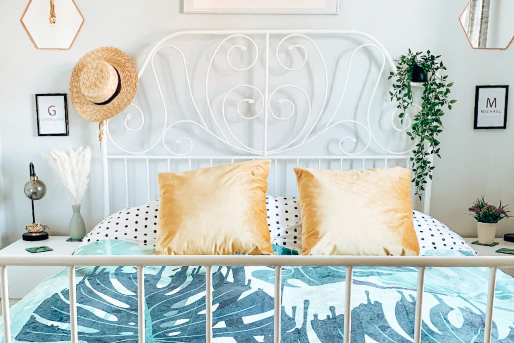 photo of a tropical blanket on a wire frame bed