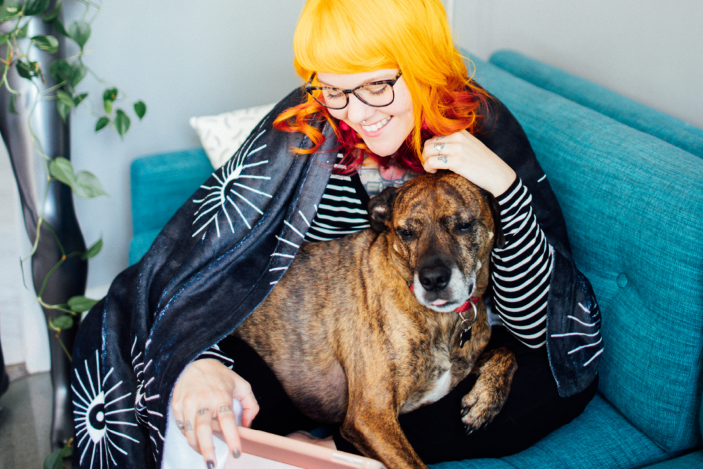 photo of a person with a throw blanket cuddling with a dog
